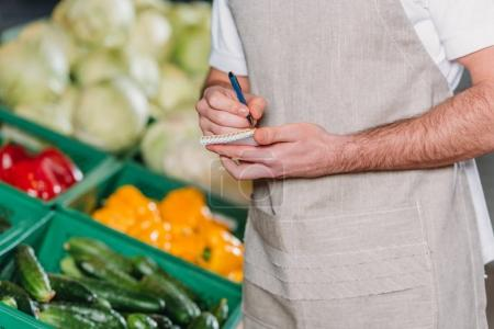 partial view of shop assistant in apron making motes in notebook in supermarket