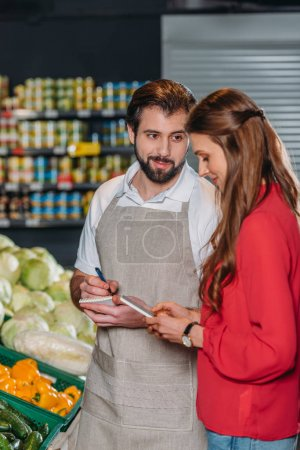 shop assistant with notebook and female shopper in supermarket