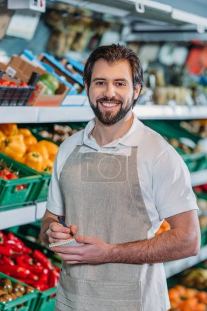 portrait of smiling shop assistant in apron with notebook in supermarket