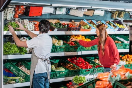 Photo for Side view of shop assistant in apron and female shopper in hypermarket - Royalty Free Image