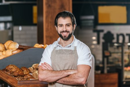portrait of smiling shop assistant in apron with arms crossed looking at camera in supermarket