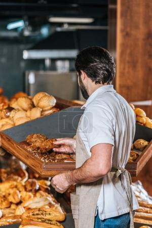 back view of male shop assistant arranging fresh bread in supermarket