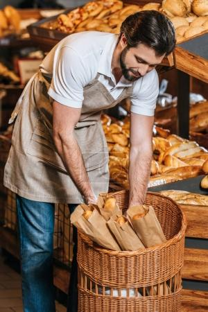 male shop assistant arranging fresh pastry in supermarket