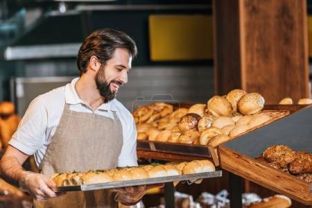 Smiling male shop assistant arranging fresh pastry...