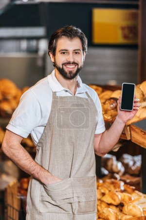 Photo for Portrait of smiling shop assistant showing smartphone with blank screen in supermarket - Royalty Free Image