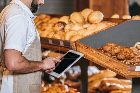 Photo pour Plan recadré de l'assistant de magasin dans le tablier en utilisant une tablette avec écran blanc dans le supermarché - image libre de droit