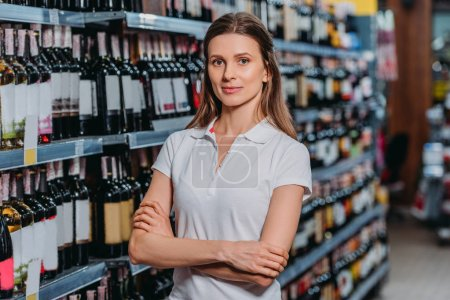 portrait of female shop assistant with arms crossed looking at camera in supermarket