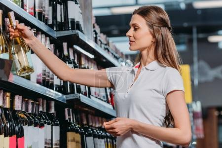side view of female shop assistant with bottle of wine in hypermarket
