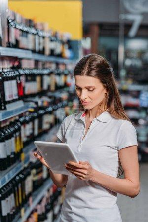 portrait of shop assistant using digital tablet in hypermarket