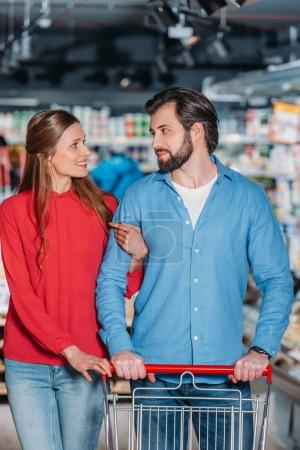 portrait of couple with shopping trolley shopping together in supermarket