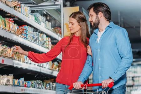 couple choosing dairy products while shopping together in supermarket