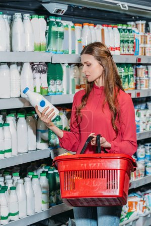 portrait of woman with shopping basket choosing dairy product in supermarket
