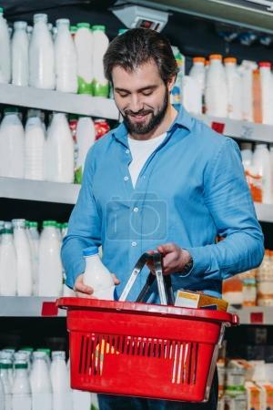 man putting bottle of milk into shopping basket in supermarket