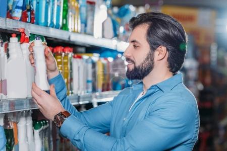 side view of man choosing detergent in hypermarket