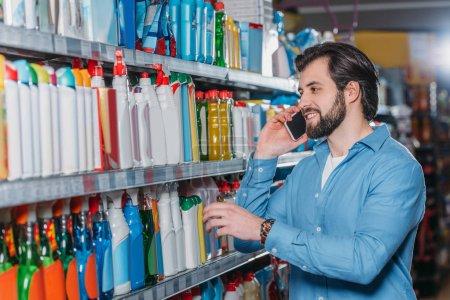 portrait of man talking on smartphone while choosing detergents in supermarket