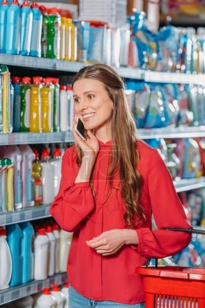 portrait of smiling woman talking on smartphone while shopping in supermarket