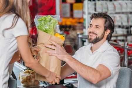 smiling shop assistant giving purchase to shopper in supermarket