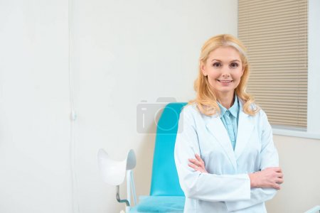 mature female gynecologist with crossed arms in front of gynecology chair
