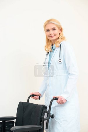 mature female doctor with wheelchair on white