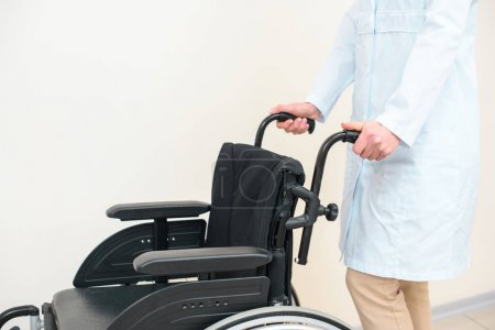 cropped shot of female doctor with wheelchair on white