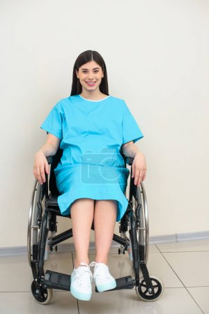 happy pregnant woman in medical coat sitting on wheelchair