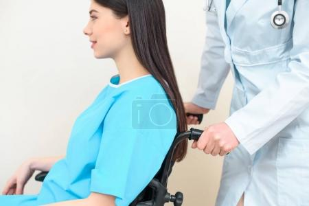cropped shot of obstetrician gynecologist riding pregnant woman on wheelchair at maternity hospital