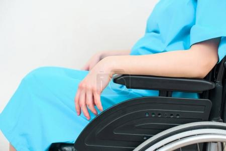 cropped shot of pregnant woman in medical coat sitting on wheelchair