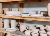 close up of ceramic plates and bowls on wooden shelves in pottery workshop