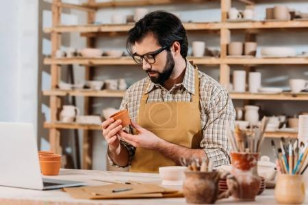 male potter in apron looking at little ceramic pot