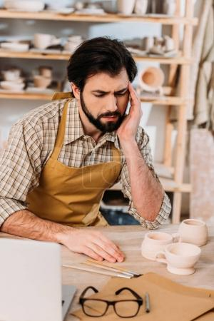 tired male potter in apron sitting in workshop