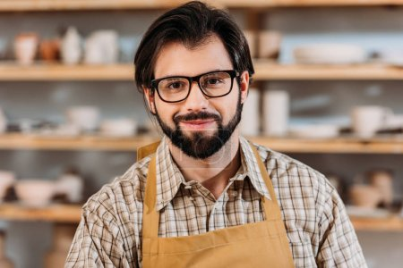 bearded potter in apron and eyeglasses in workshop