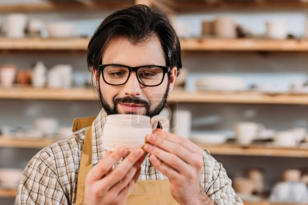 male potter looking at ceramic cup in workshop