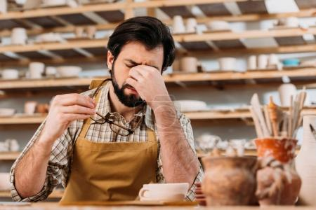 bearded tired potter in apron sitting in workshop with ceramic dishware on shelves
