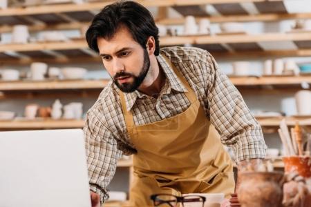 Photo pour Potier masculin dans tablier de travail avec ordinateur portable dans l'atelier - image libre de droit
