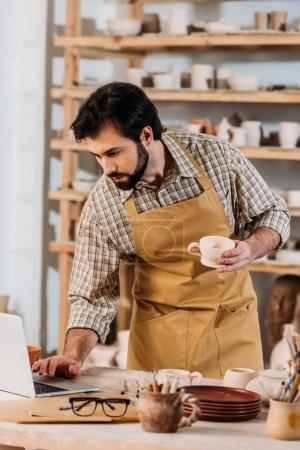 male potter in apron holding ceramic cup and using laptop in workshop
