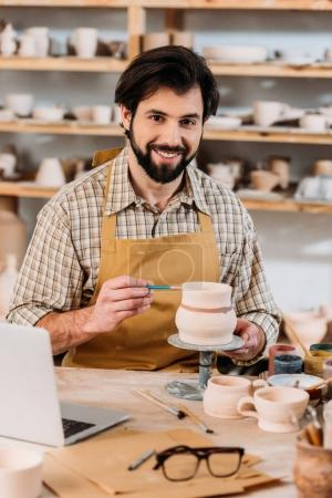 happy male potter painting ceramic dishware in workshop with laptop on table