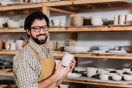 Photo pour Souriant potter tenant la tasse en céramique dans l'atelier avec la vaisselle sur les tablettes - image libre de droit