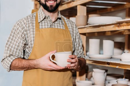 cropped view of male potter holding ceramic cup and standing near shelves with dishware