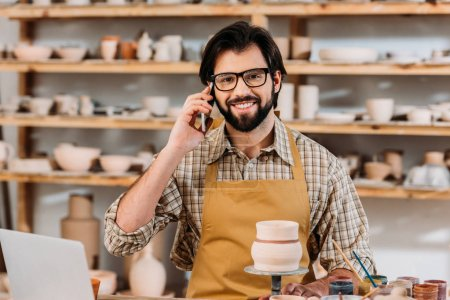 Photo for Smiling male potter talking on smartphone in workshop - Royalty Free Image