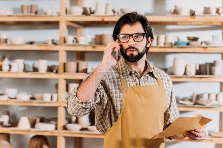 male potter holding envelope and talking on smartphone in workshop