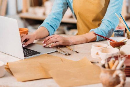 cropped view of woman working with laptop in pottery workshop