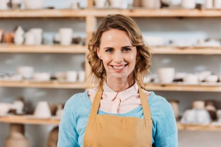 Photo for Beautiful cheerful woman in apron standing in pottery workshop - Royalty Free Image