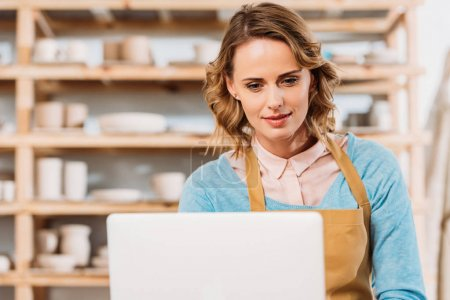 Photo for Beautiful woman in apron using laptop in pottery workshop - Royalty Free Image
