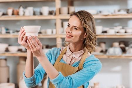 beautiful female potter holding ceramic bowl in workshop