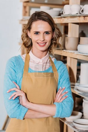 beautiful smiling potter with crossed arms standing near shelves with ceramic dishware