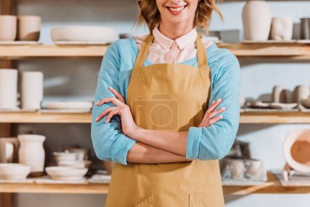 cropped view of potter with crossed arms standing near shelves with ceramic dishware