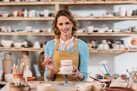 smiling woman in apron painting ceramic dishware in pottery workshop