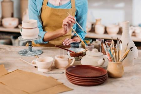 cropped view of potter in apron painting ceramic dishware in workshop