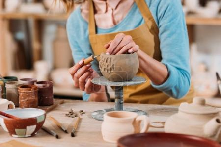 cropped view of potter in apron decorating ceramic bowl in workshop