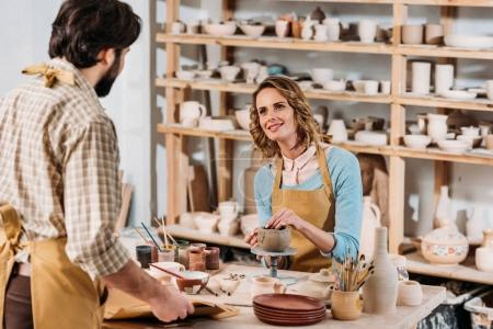 man with papers and female potter with ceramics in workshop